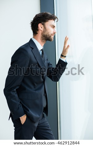 businessman in suit standing next to an office building window