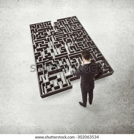 businessman in suit standing on labyrinth - stock photo