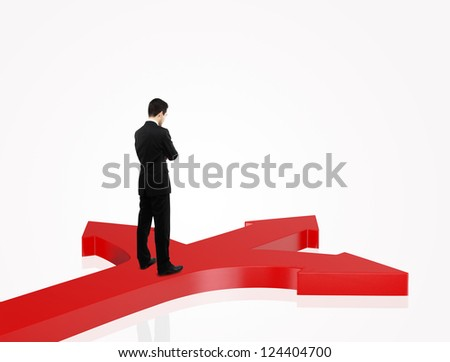 businessman in suit standing on red arrows - stock photo