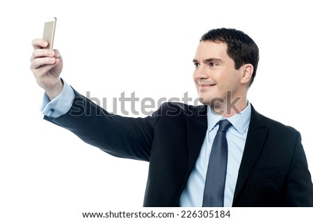 Businessman in suit taking a photo using his mobile phone - stock photo
