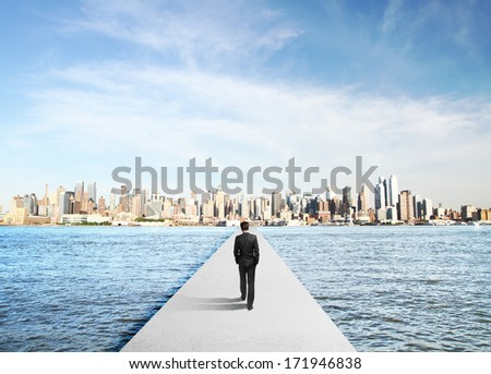 businessman in suit walking to city on concrete bridg - stock photo
