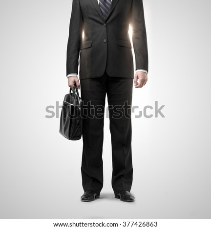businessman in suit with black briefcase on gray background