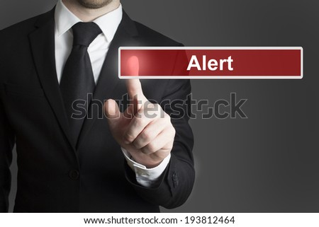 businessman in suite pressing touchscreen alert - stock photo