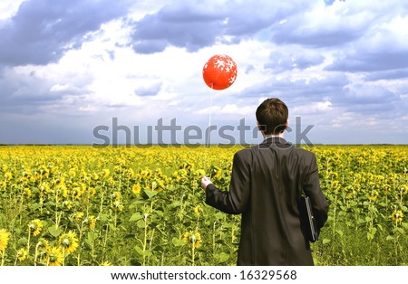 Businessman in sunflowers with red balloon