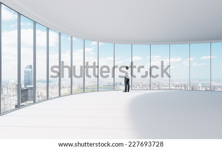 Businessman in the contemporary Manhattan office looking at the city.  - stock photo