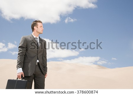 Businessman in the desert - stock photo