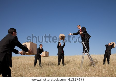 businessman in the field delivering a package - stock photo
