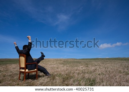 businessman in the field sited in a chair with his arms outstretched - stock photo