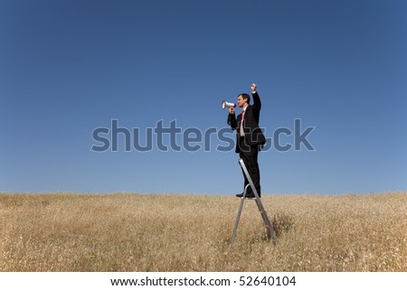 businessman in the field speaking to nobody - stock photo