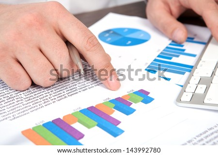 businessman in the office of the table points to the graphics - stock photo