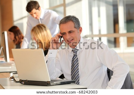 Businessman in the office talking on the phone - stock photo