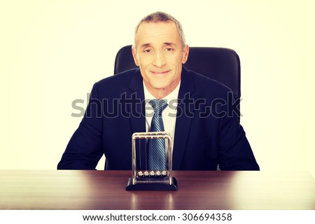 Businessman in the office with newton balls.
