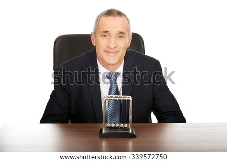 Businessman in the office with newton balls. - stock photo