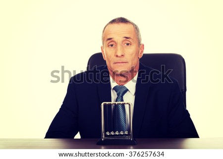 Businessman in the office with newton balls - stock photo
