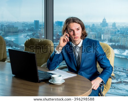 Businessman in the office with panoramic windows on the computer