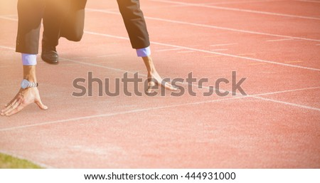 Businessman in the starting blocks against view of a running track