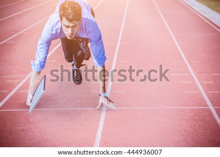 Businessman in the starting blocks holding a laptop against focus of athletics track