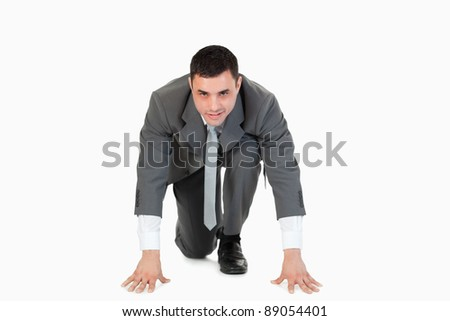 Businessman in the starting blocs against a white background - stock photo