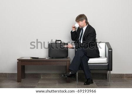 Businessman in the waiting room drinking coffee.