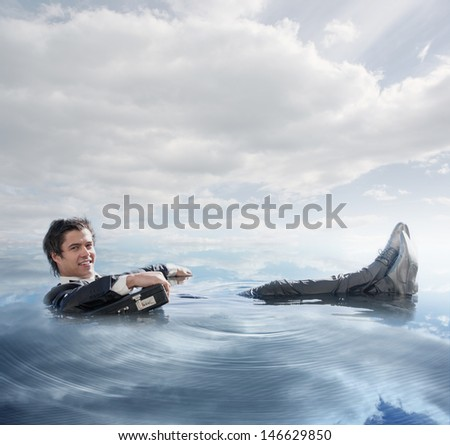 Businessman in the water lying on the back smiling at camera in blue sky background
