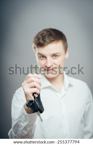 Businessman in tie holding key with focus on key. Holding out keys and smiling on grey background