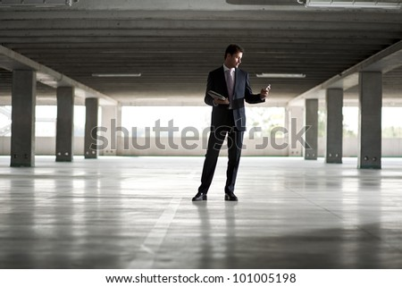 Businessman in underground parking holding tablet and mobile phone - stock photo