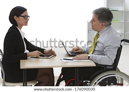 Businessman in wheelchair  having a meeting with Businesswoman Meeting In Office  - stock photo