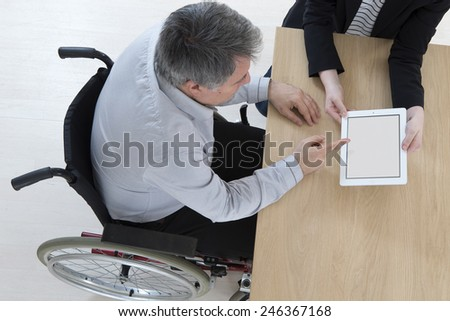 Businessman in wheelchair with his personal assistant   in the office - stock photo