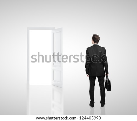 businessman in white room with doors open - stock photo