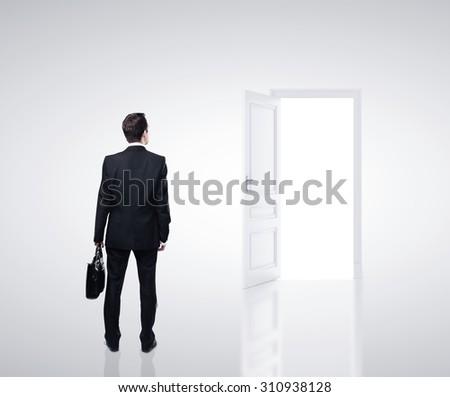 businessman in white room with open door - stock photo