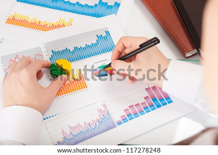 Businessman in white shirt analyzing charts and graphs - stock photo
