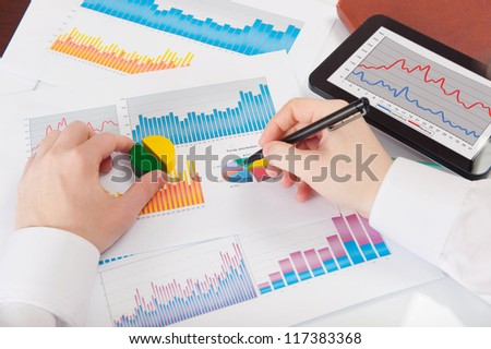 Businessman in white shirt analyzing graphs. Rear view - stock photo