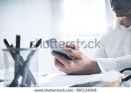 Businessman in white shirt sitting at his office and using modern smart phone. Young man with cellphone, with documents on a desk - stock photo