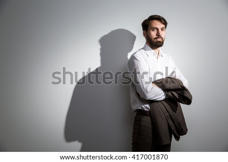 Businessman in white shirt with his suit jacket in hands standing against wall with shadow - stock photo