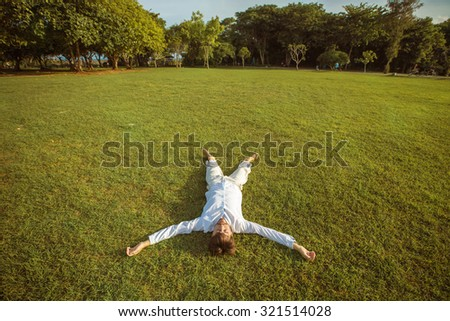 Businessman in White suit on vacation lying on Green  grass happy resting and relaxing. Time for new ideas, freedom concept - stock photo