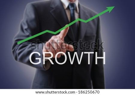 Businessman indicating the growth with his forefinger