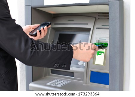 businessman inserts a credit card into the ATM to withdraw money and holding a phone - stock photo