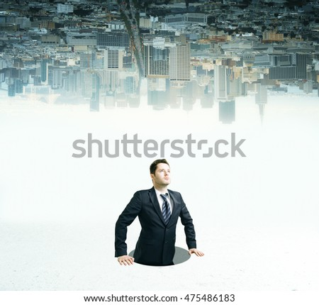 Businessman inside hole looking up on upside down city background