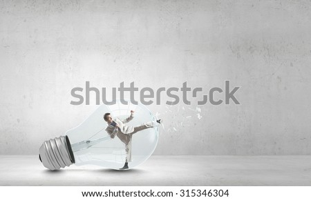 Businessman inside light bulb braking it to get out - stock photo