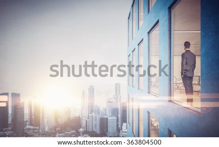 Businessman inside skyscraper, lookng at the city through  window. Horizontal - stock photo