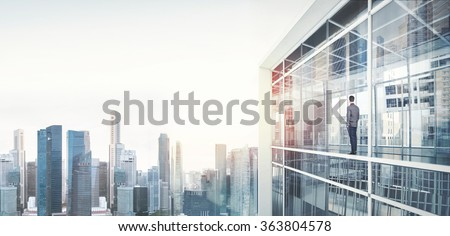 Businessman inside skyscraper, lookng at the city through  window on sunrise - stock photo