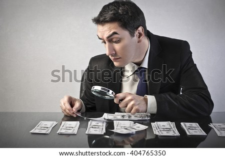 Businessman inspecting banknotes - stock photo