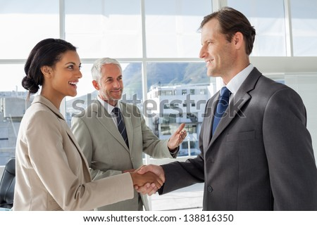 Businessman introducing a colleague to another businessman - stock photo