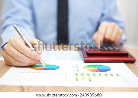 businessman is analyzing report and using calculator - stock photo