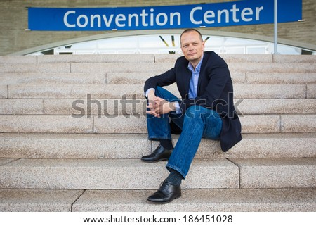 Businessman is attending a convention and sits in front of the entrance of the convention center - stock photo