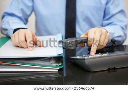 Businessman is calling for support when received a lot of documentation. consultant  is required - stock photo