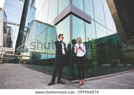 Businessman is calling via cellphone, while his secretary standing near with mobile phone in hands. Two smart managers are using their cell telephones during work break, while are standing outdoors - stock photo