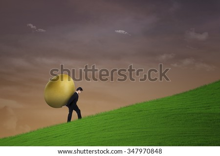 Businessman is carrying gold egg on steep hill - stock photo