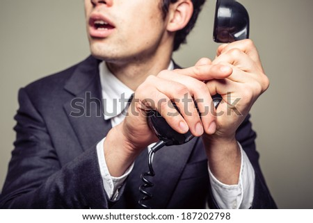 Businessman is covering the phone to speak in private to someone in the room - stock photo