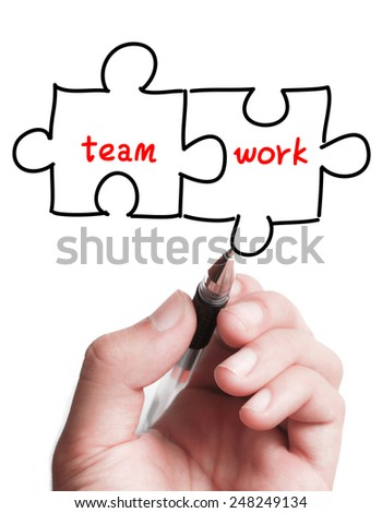 Businessman is drawing a Teamwork puzzle concept on the transparent virtual screen. - stock photo